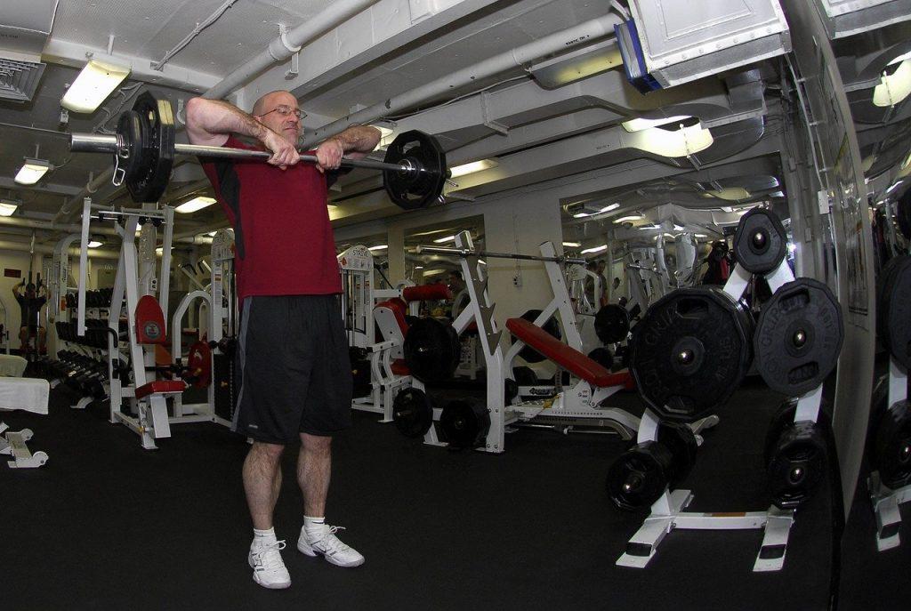 homme senior entrain de suivre un programme de fitness en salle de gym